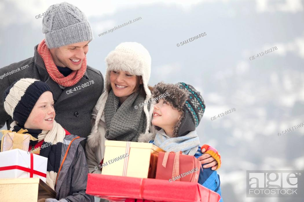 Stock Photo: Happy family carrying Christmas gifts in snow.