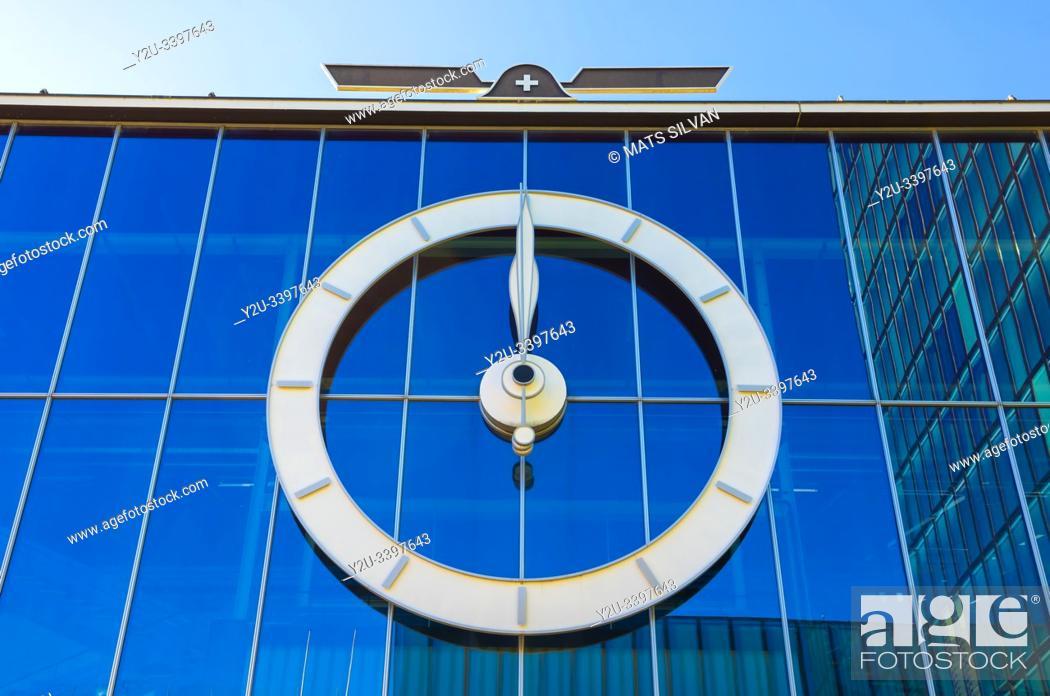 Stock Photo: Big Clock on Glass Facade in Basel, Switzerland.
