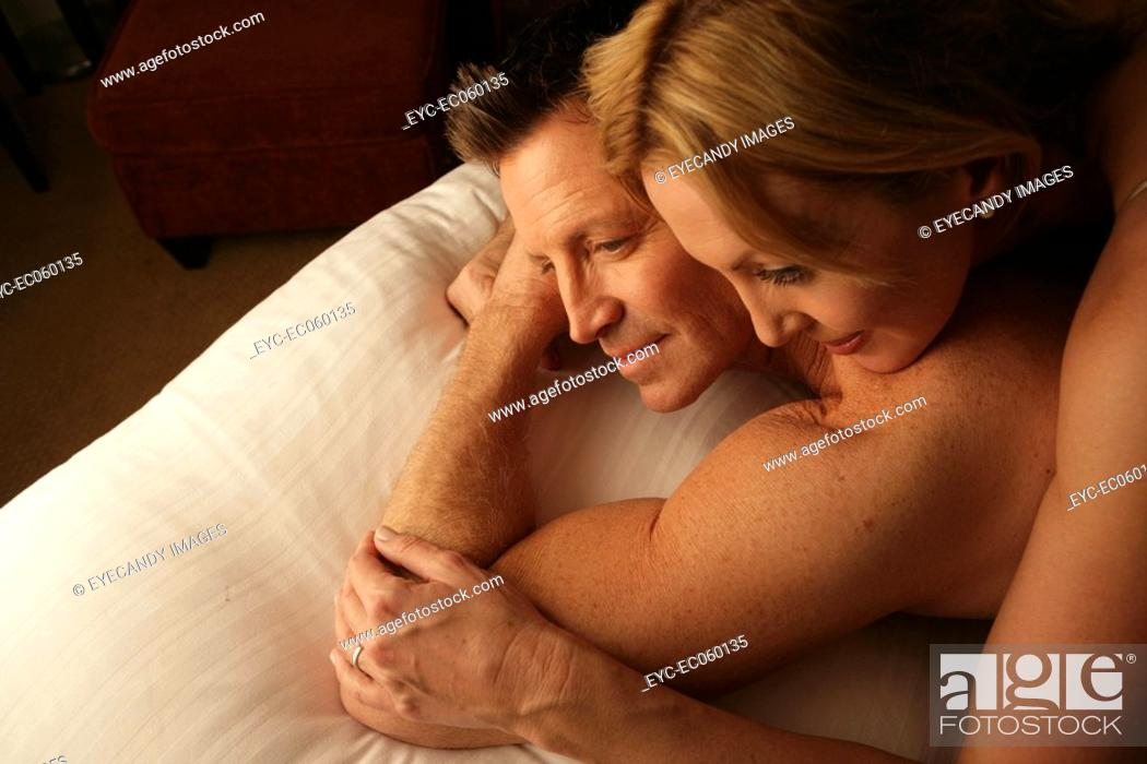 Stock Photo: Mature couple in bed smiling.