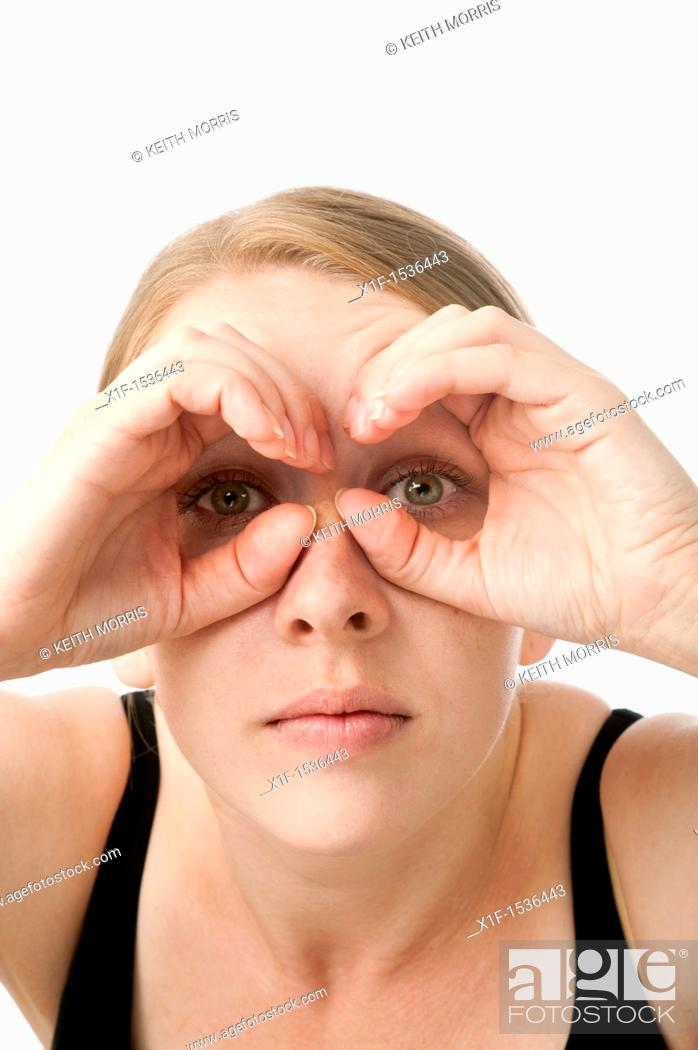Stock Photo: a young caucasian woman looking through her hands shaped like binoculars, uk.