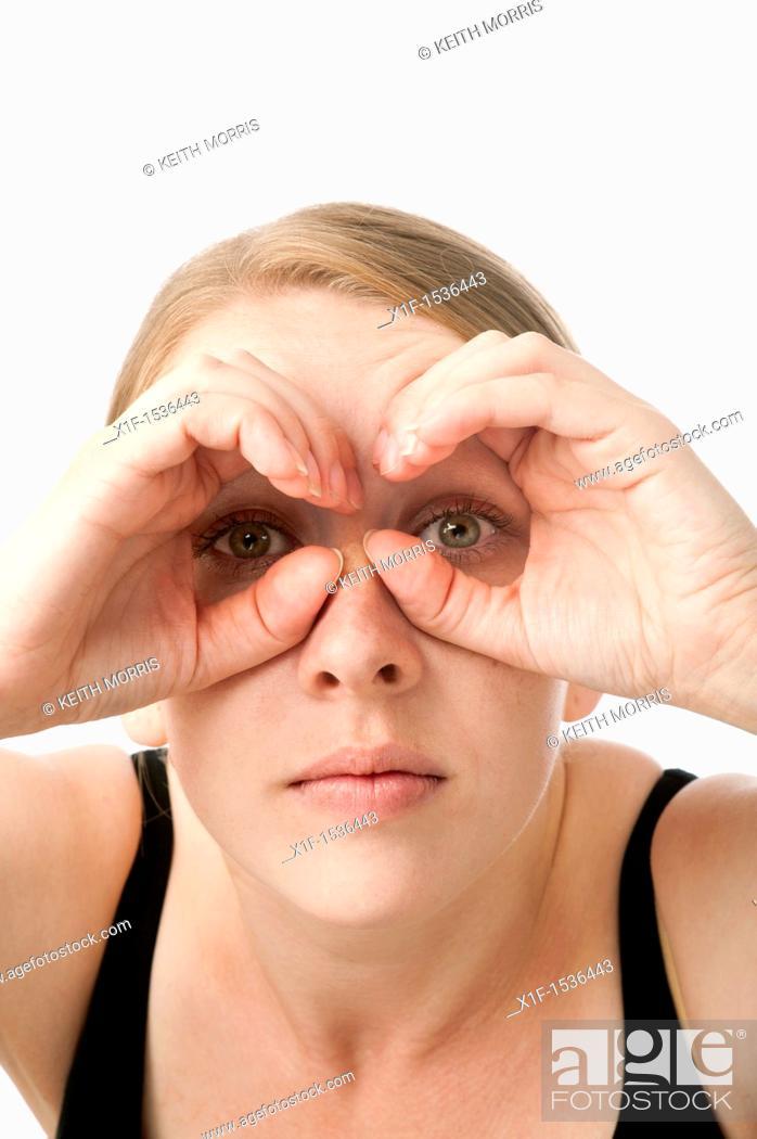 Stock Photo: a young caucasian woman looking through her hands shaped like binoculars, uk.