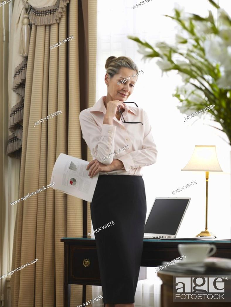 Stock Photo: Business woman holding document standing in home office.