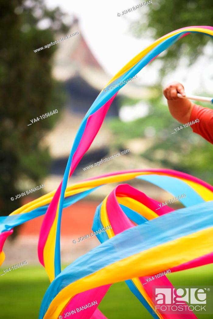 Stock Photo: Coloured ribbon twirled by women in the park for recreation.