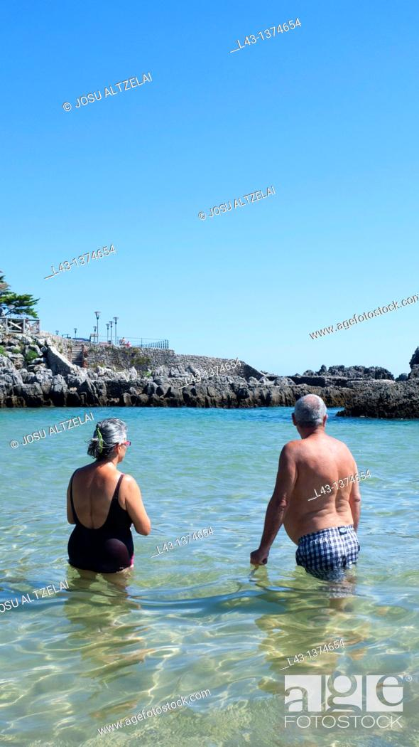 Stock Photo: Old couple having a bath in the beach of Isla,province of cantabria,spain.