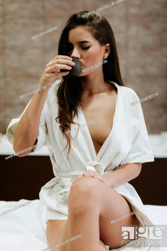 Stock Photo: Young woman sitting on lounger in a spa drinking cup of tea.