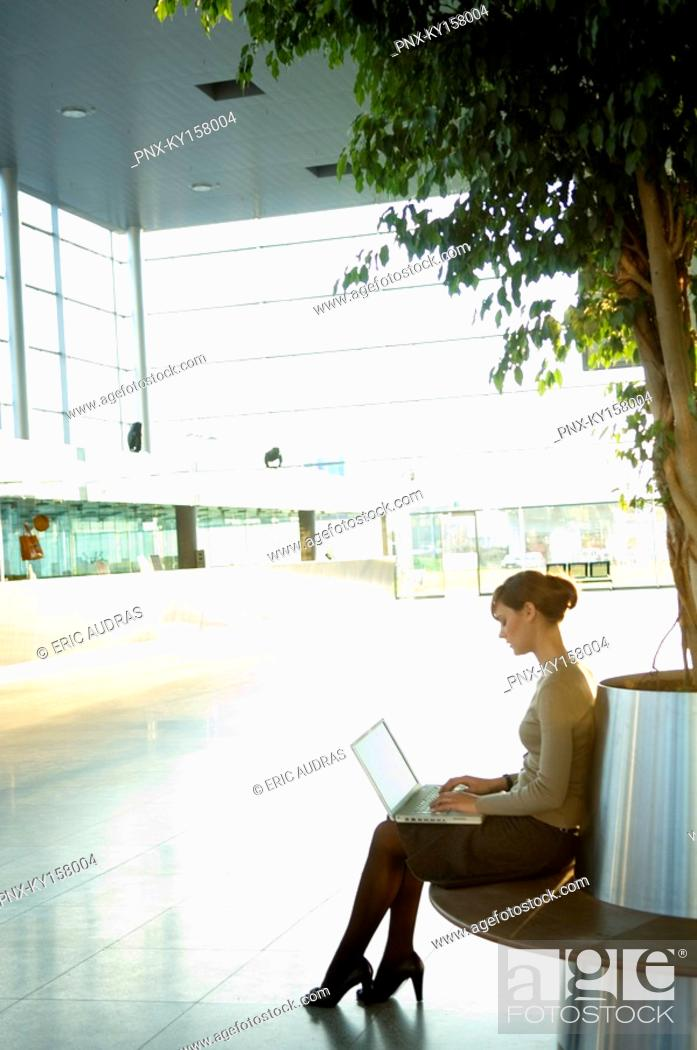 Stock Photo: Side profile of a businesswoman working on a laptop.