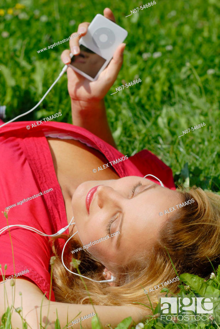 Stock Photo: Young girl with a red dress enjoying mp3 music and relaxing.