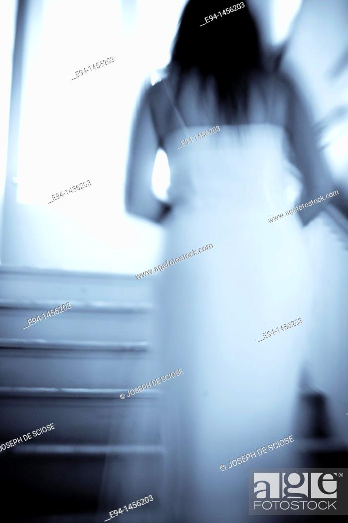 Stock Photo: Blurry back view of a woman in a white dress walking up a stairway, indoors.