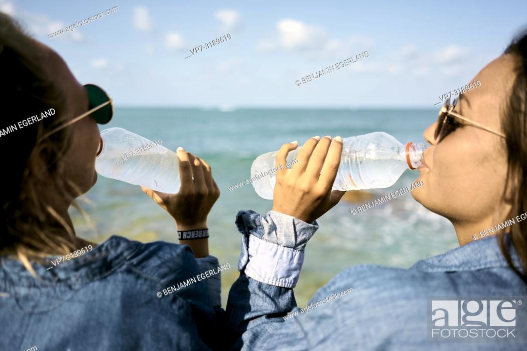 Stock Photo: Two women sitting at beach drinking water from plastic bottles, Chersonissos, Crete, Greece.