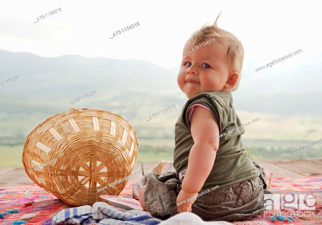 Stock Photo: Baby girl sitting on the ground, looking back.