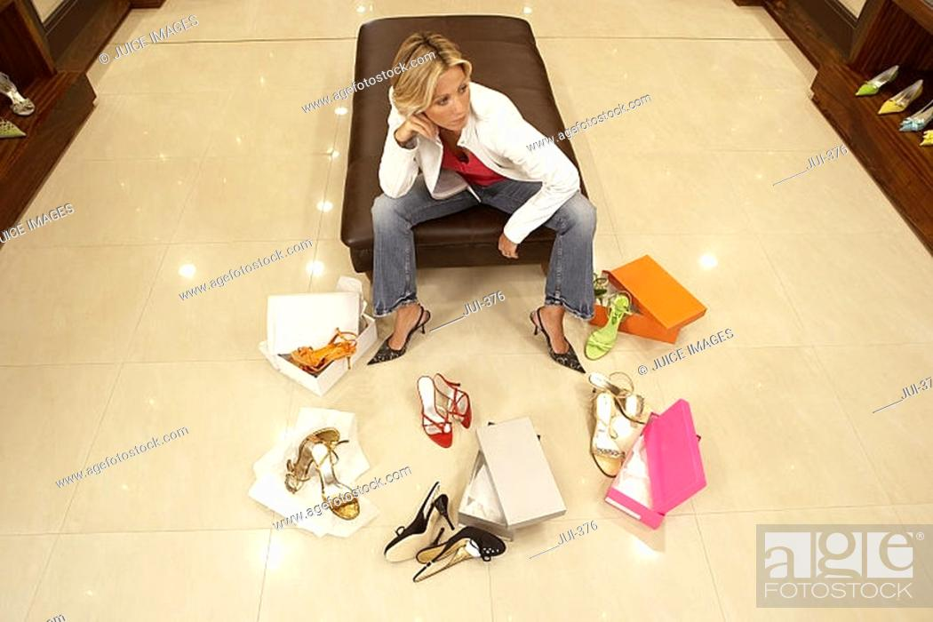 Stock Photo: Mature blonde woman trying on different pairs of high heels in shoe shop, thinking, elevated view.