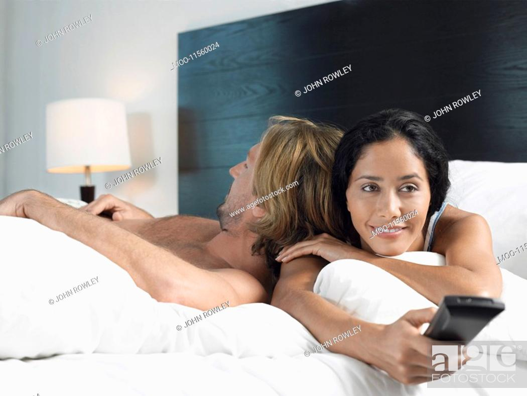 Stock Photo: Couple Watching TV and Relaxing on Bed.