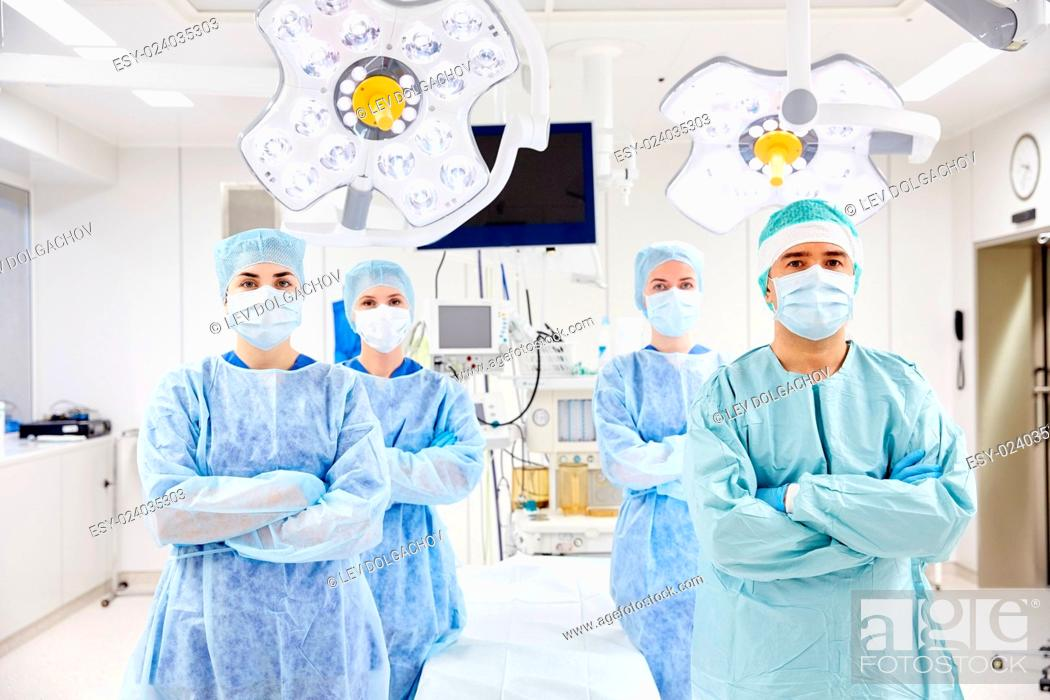 Stock Photo: surgery, medicine and people concept - group of surgeons in operating room at hospital.