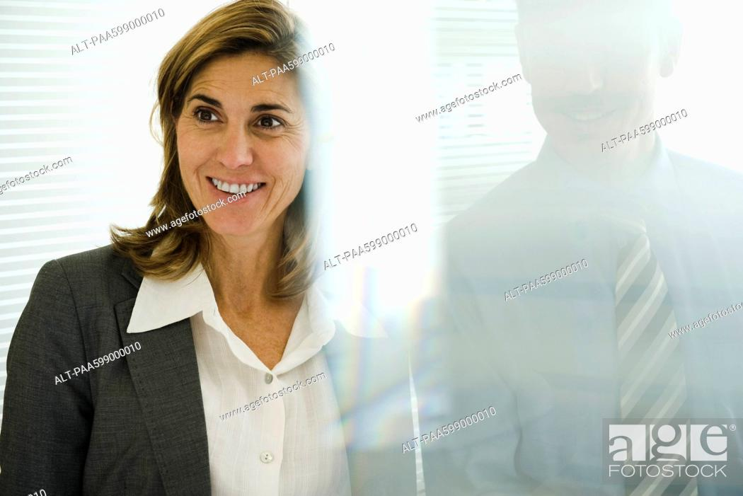 Stock Photo: Smiling businesswoman looking away, businessman behind glass wall.