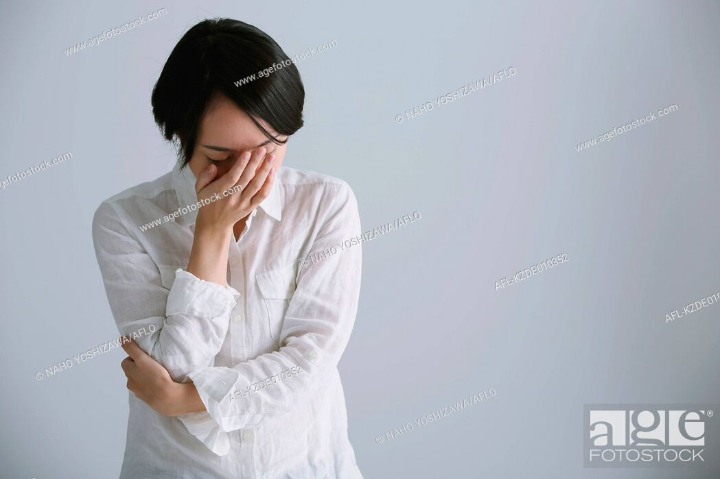 Stock Photo: Desperate Japanese young woman in a white shirt.