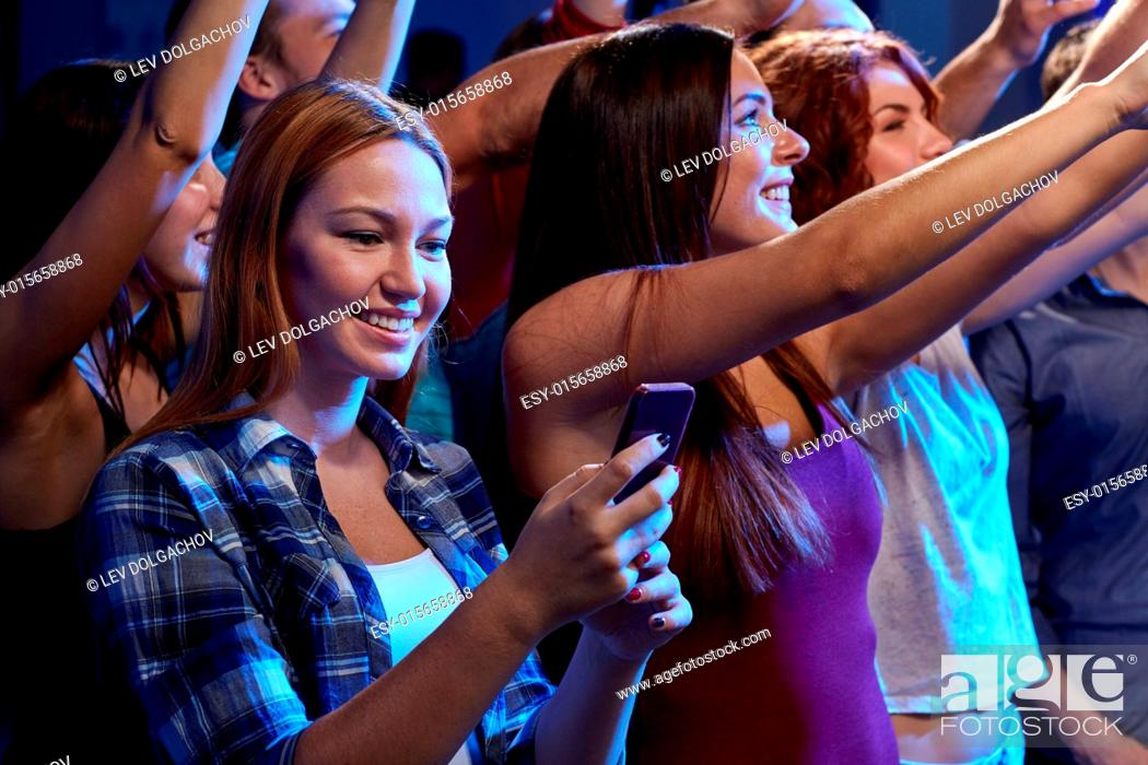 Stock Photo: party, holidays, celebration, nightlife and people concept - smiling young woman with smartphone texting message at concert in club.