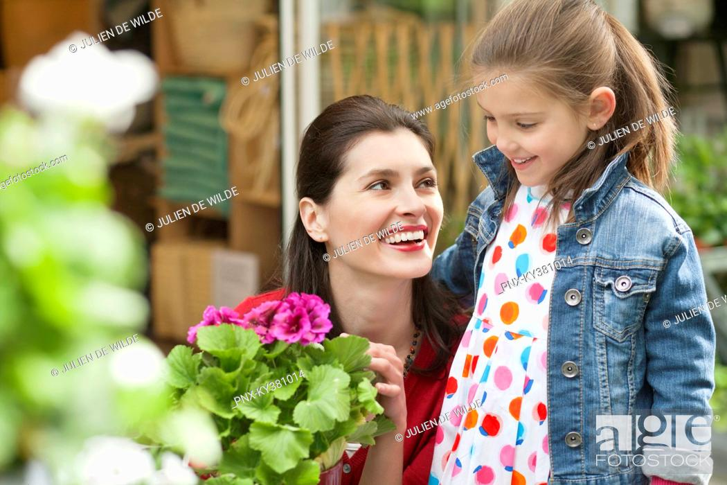 Stock Photo: Woman and her daughter looking at flowers in a flower shop.