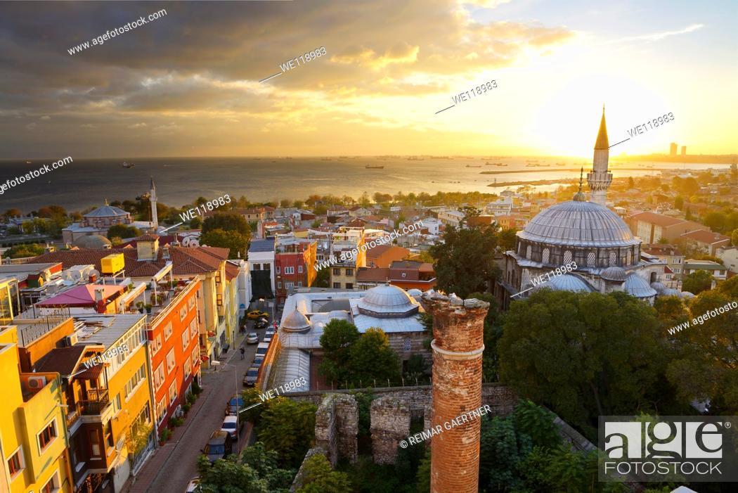 Stock Photo: Setting sun behind the Sokollu Mehmet Pasha mosque minaret with golden glow on houses and Marmara Sea Istanbul.
