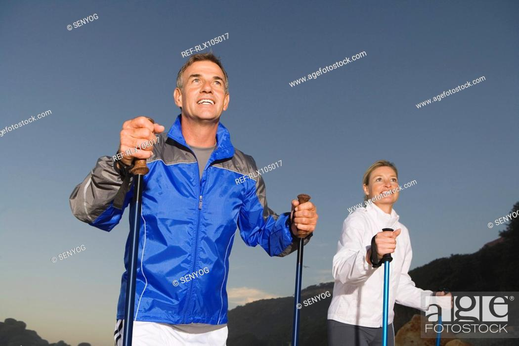 Stock Photo: Senior couple wearing tracksuit doing Nordic Walking at sunset.