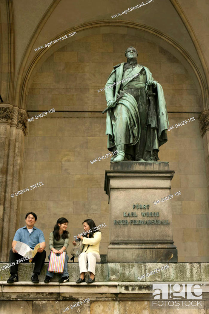 Stock Photo: Three Asian people sitting on the top stairs of a monument.