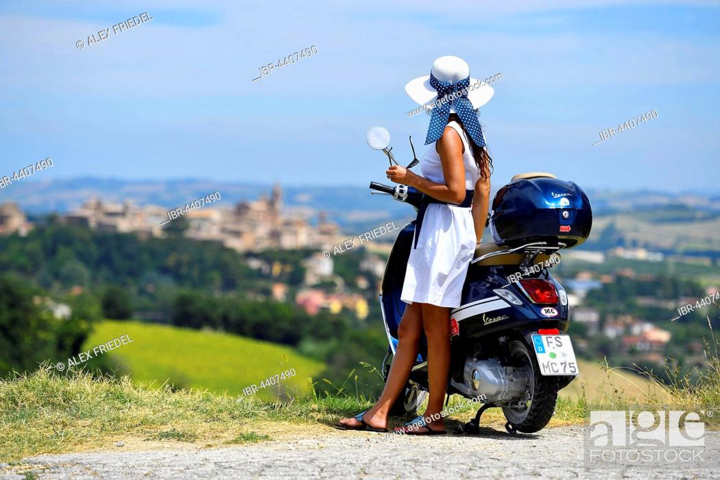 Stock Photo: Woman with white sunhat next to Vespa Primavera scooter, Corinaldo, Marche, Italy.