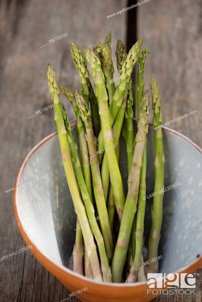 Stock Photo: Green asparagus. Uncooked vegetables in a bowl. Fresh harvest of spring vegetable.