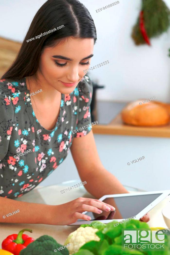 Stock Photo: Young hispanic woman or student cooking in kitchen. Girl using tablet to make online shopping or find a new recipe.