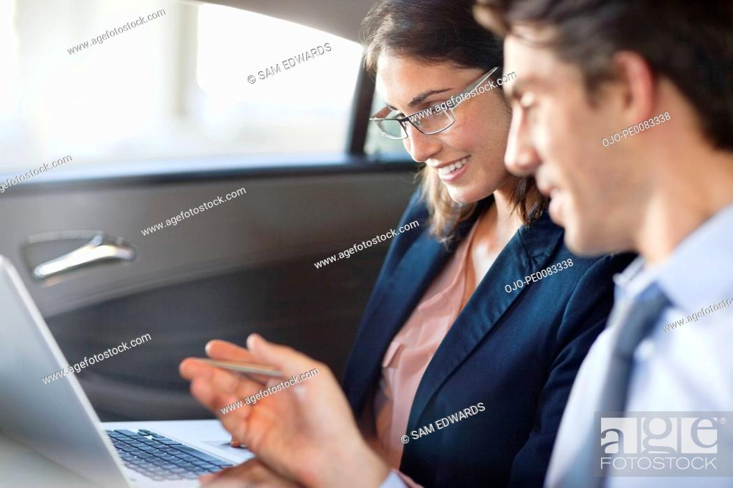 Stock Photo: Businessman and businesswoman using laptop in back seat of car.