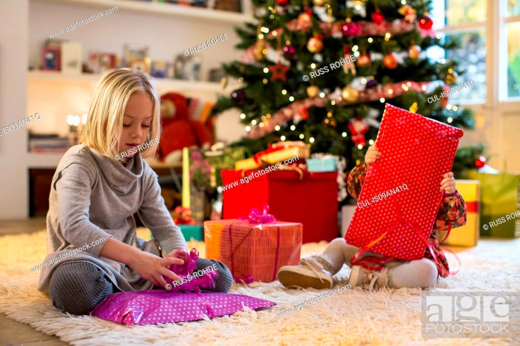Stock Photo: Sisters checking presents by Christmas tree.