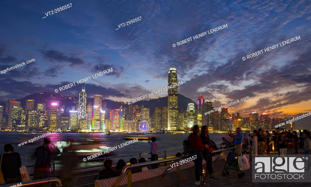 Stock Photo: The famous Tsim Sha Tsui promenade, and tourists enjoying the evening view of Hong Kong Island, Hong Kong, China.
