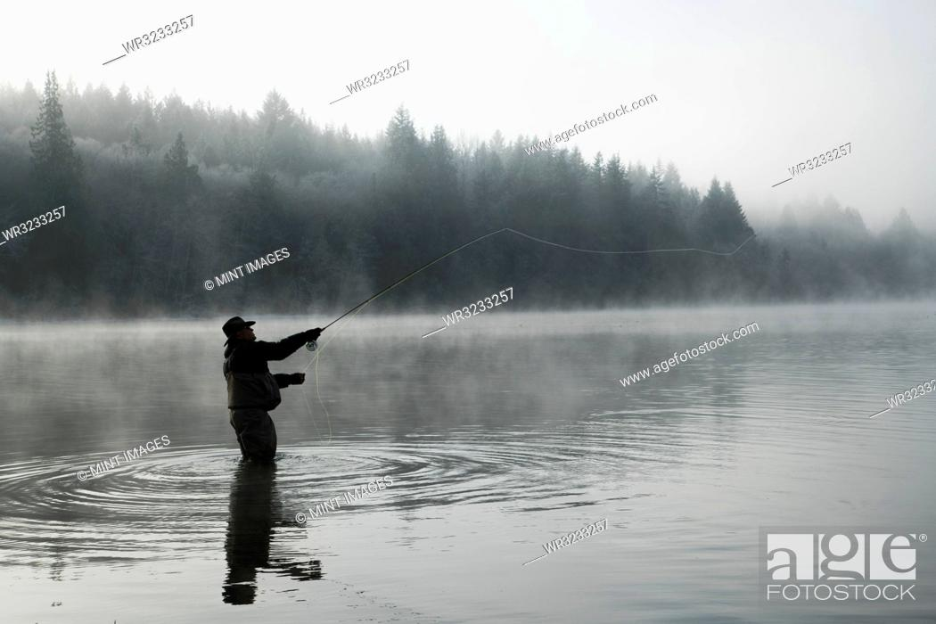 Imagen: Silhouette of fisherman fly fishing for salmon and sea run cutthroat trout.