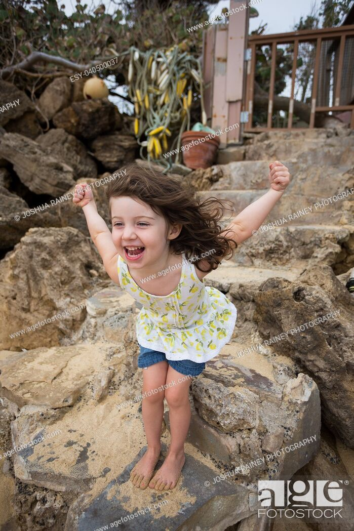 Stock Photo: Fun fashion lifestyle portrait of a young three year old girl sitting on some stone stairs at the beach in Oahu Hawaii.
