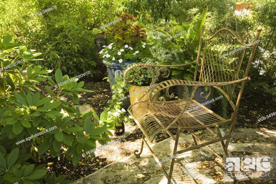 Stock Photo: Nuanced wrought iron metal sitting chair on flagstone patio in backyard country garden in summer.