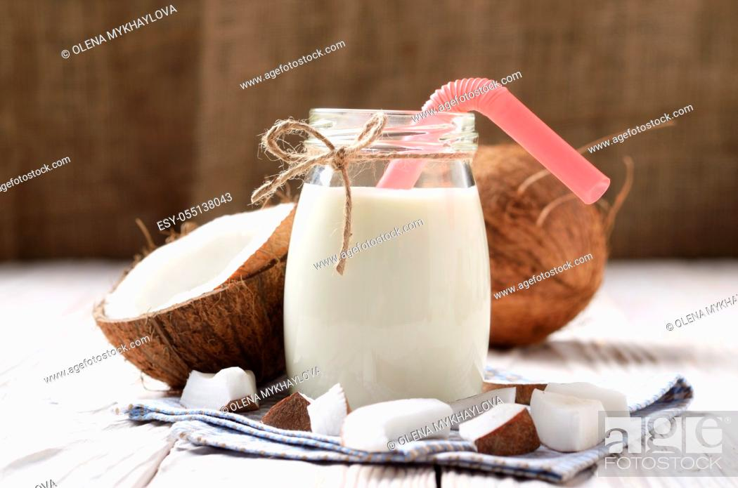 Stock Photo: Mason jar of milk or yogurt on blue napkin on white wooden table with coconut aside.