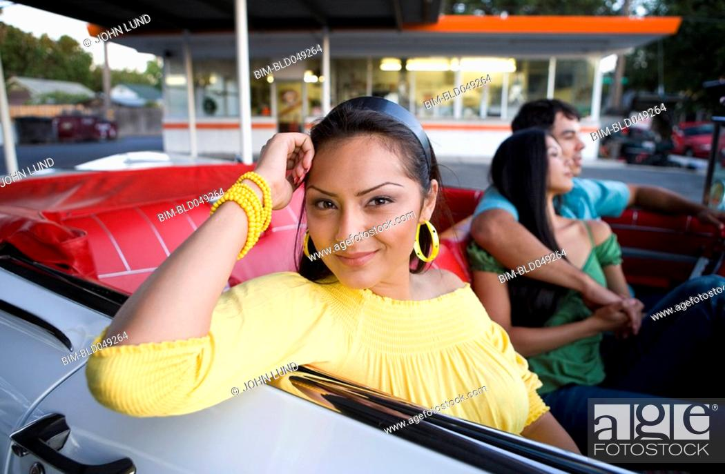 Stock Photo: Hispanic woman with friends in convertible.