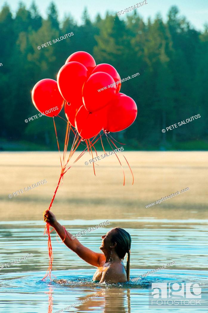 Stock Photo: Woman in water holding bunch of red balloons.