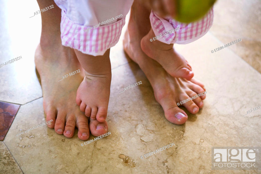 Stock Photo: Close-up of mother and infant girl's barefeet. Infant is standing on mother's feet.
