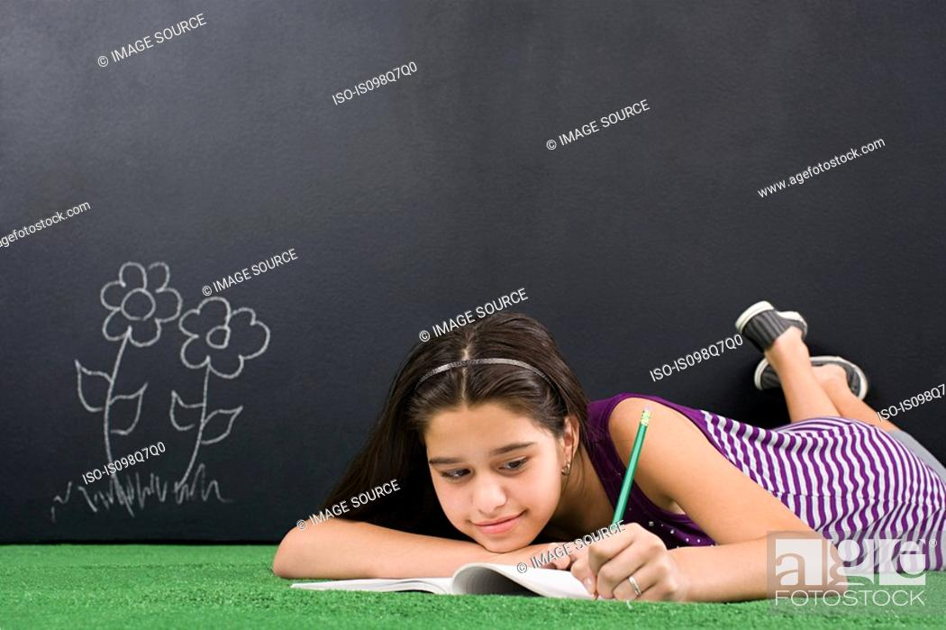 Stock Photo: A girl writing in notebook.