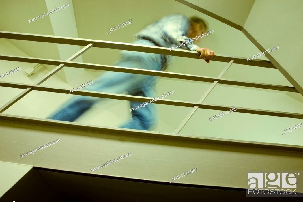 Stock Photo: Man on a walkway in an office building.