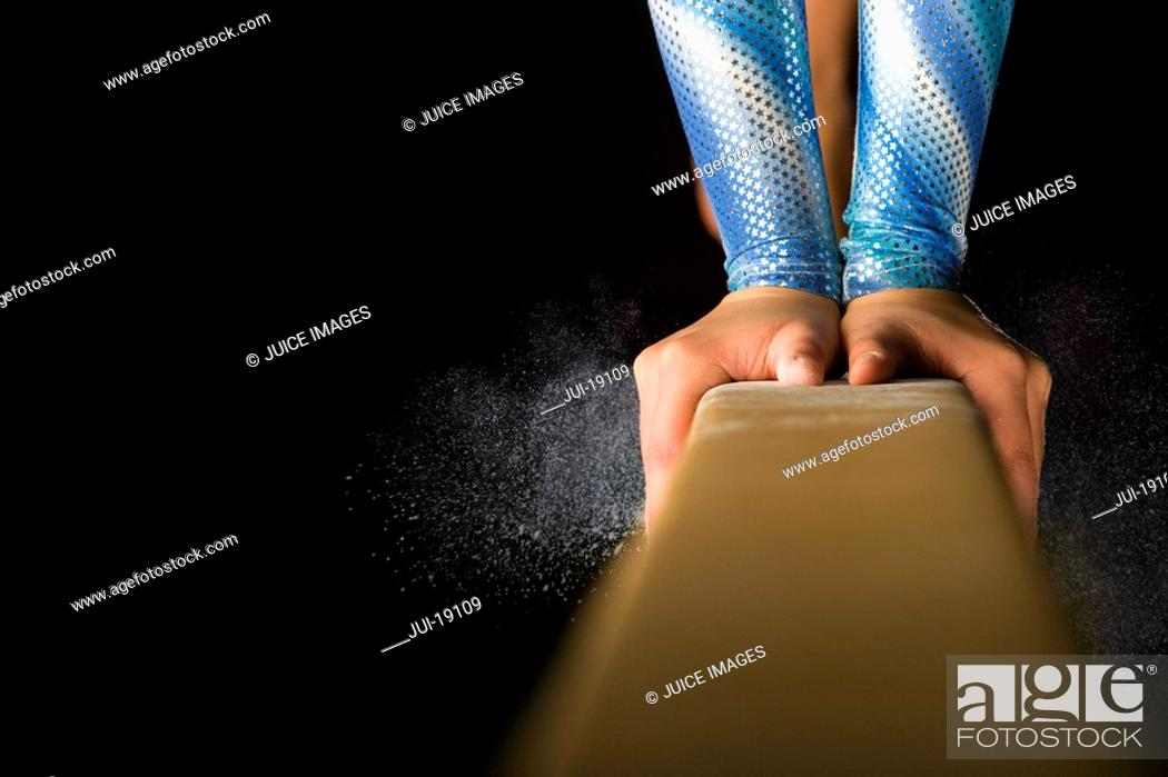Stock Photo: Female gymnast performing on balance beam, close-up of hands.