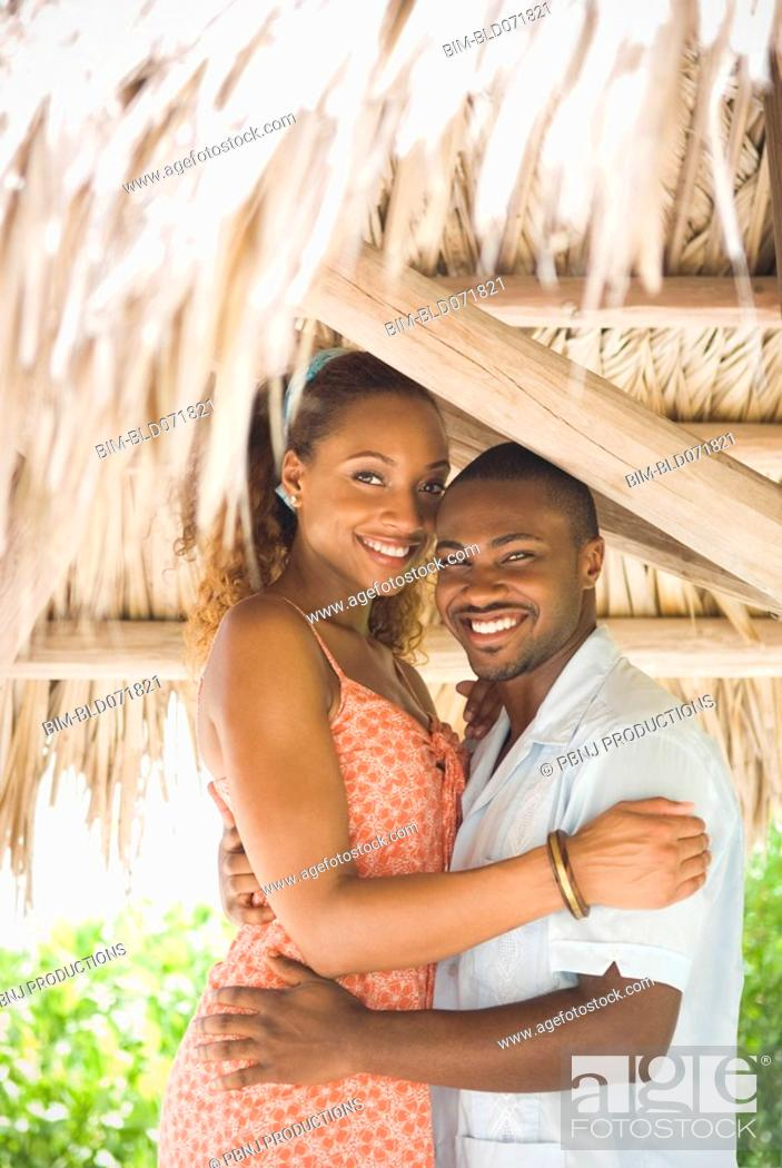Stock Photo: African American couple hugging in grass hut.