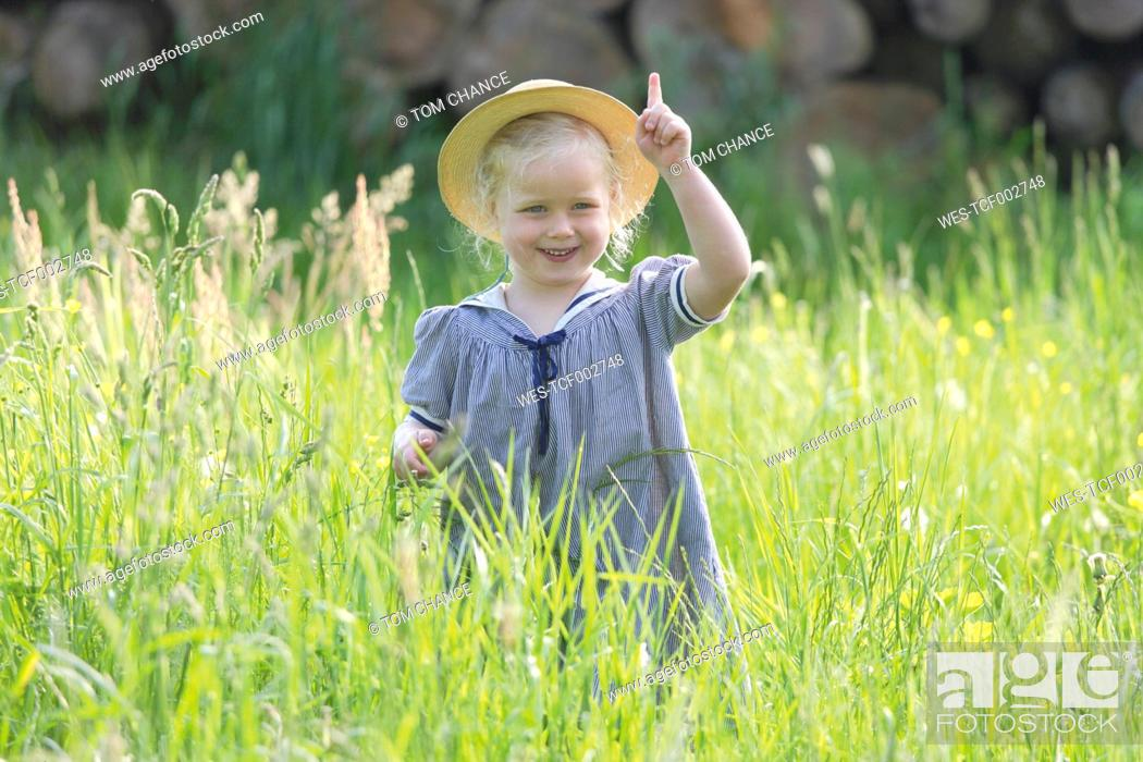 Stock Photo: Germany, Bavaria, Girl standing in meadow, smiling, portrait.