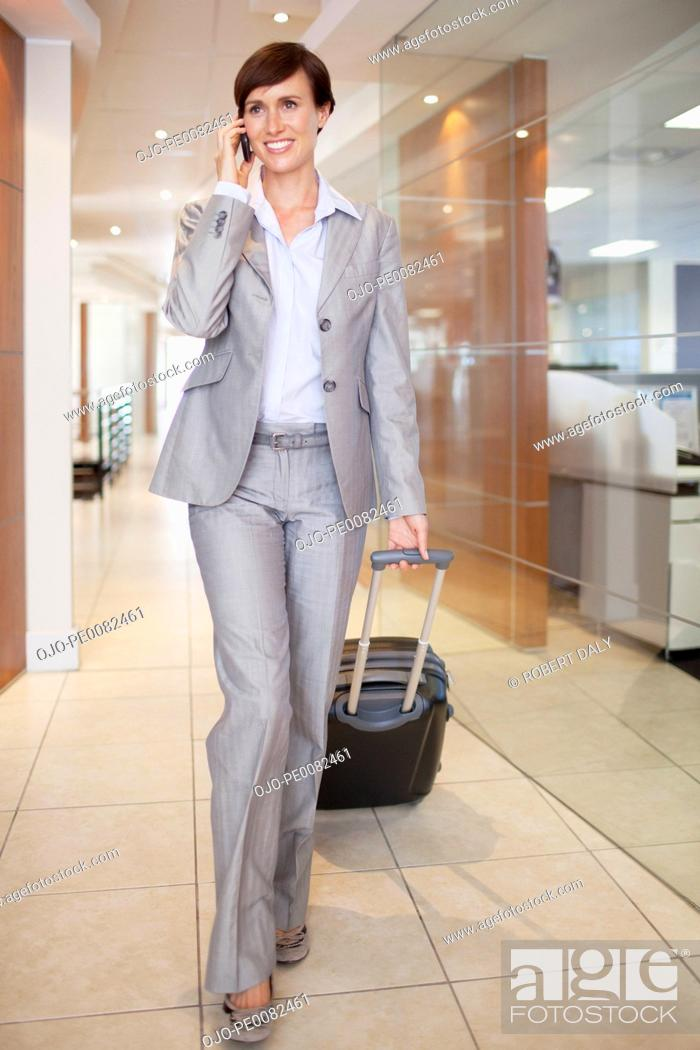 Stock Photo: Businesswoman talking on cell phone and pulling suitcase in corridor.