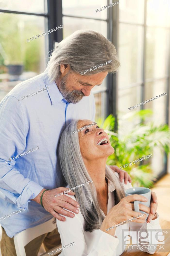 Stock Photo: Happy senior couple drinking coffee at home.