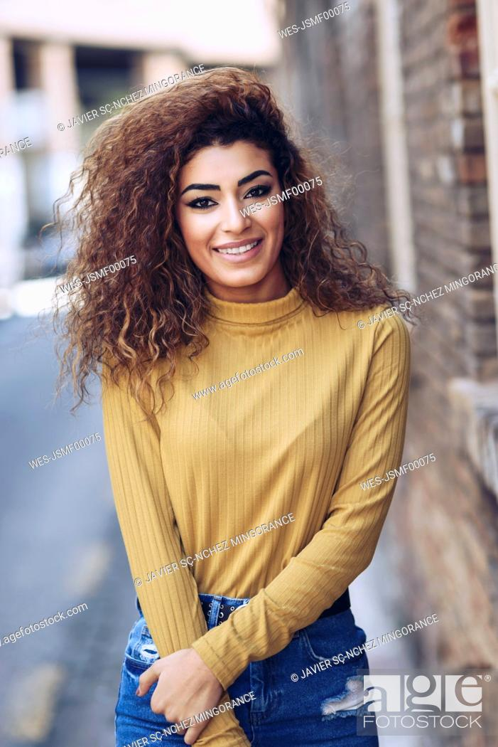 Stock Photo: Portrait of smiling young woman with curly hair.