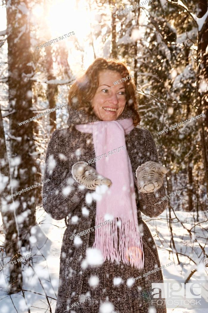 Photo de stock: Happy red-haired woman having fun on winters day in forest. Latvia.