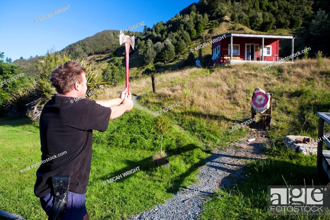 Stock Photo: A Man Takes An Attempt At An Axe Throw At Blue Duck Lodge, In Whanganui National Park; Whakahoro, New Zealand.