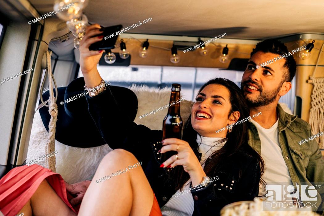 Stock Photo: Happy young couple taking a selfie inside camper van.