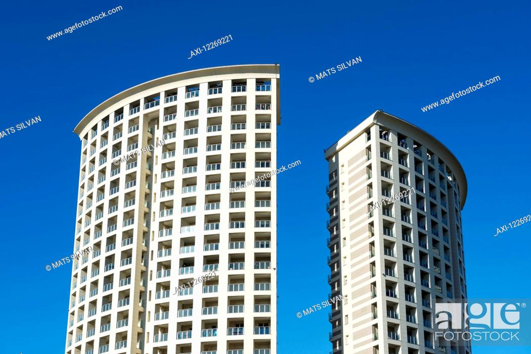 two rounded residential buildings side by side against a blue sky
