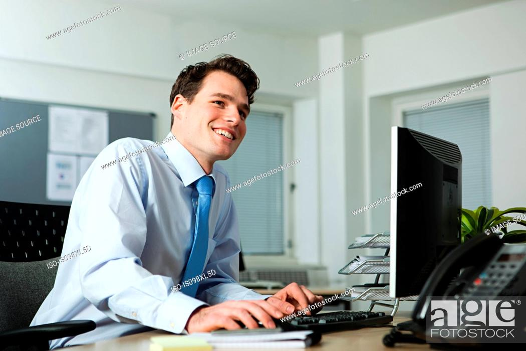 Stock Photo: Office worker sitting at desk, smiling.